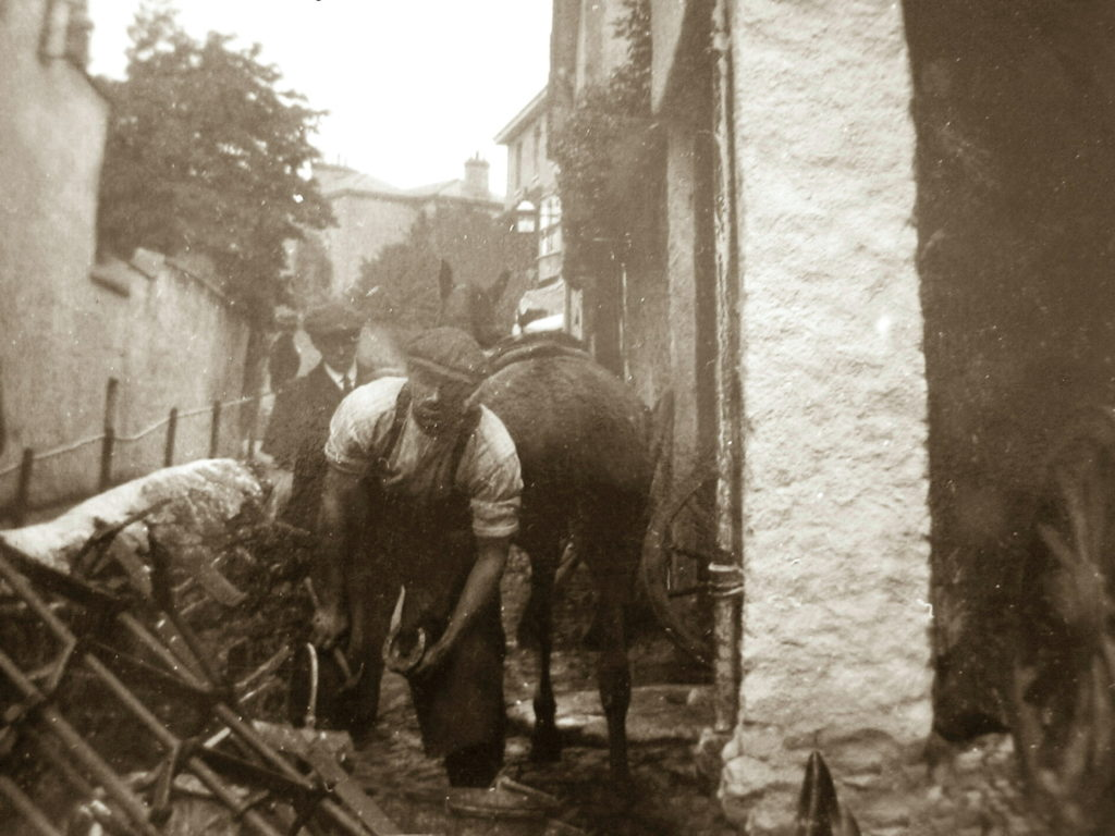 Sepia Photograph Gordon Major outside Fore Street Smithy