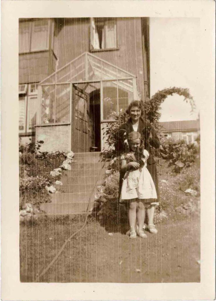 Photograph of Grace Coombe née Loud and Molly Coombe outdoors with cats.