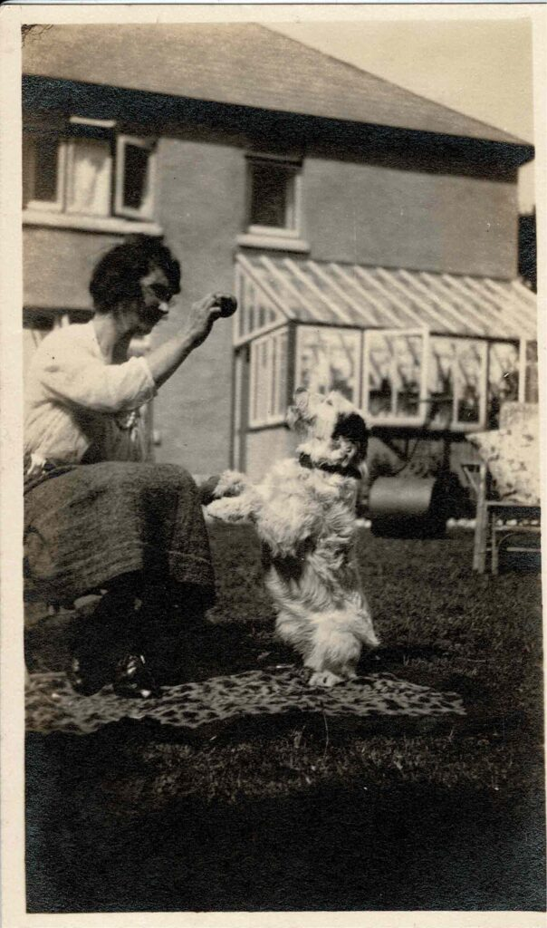 Photograph of Grace Coombe née Loud playing with a dog, around 1930.
