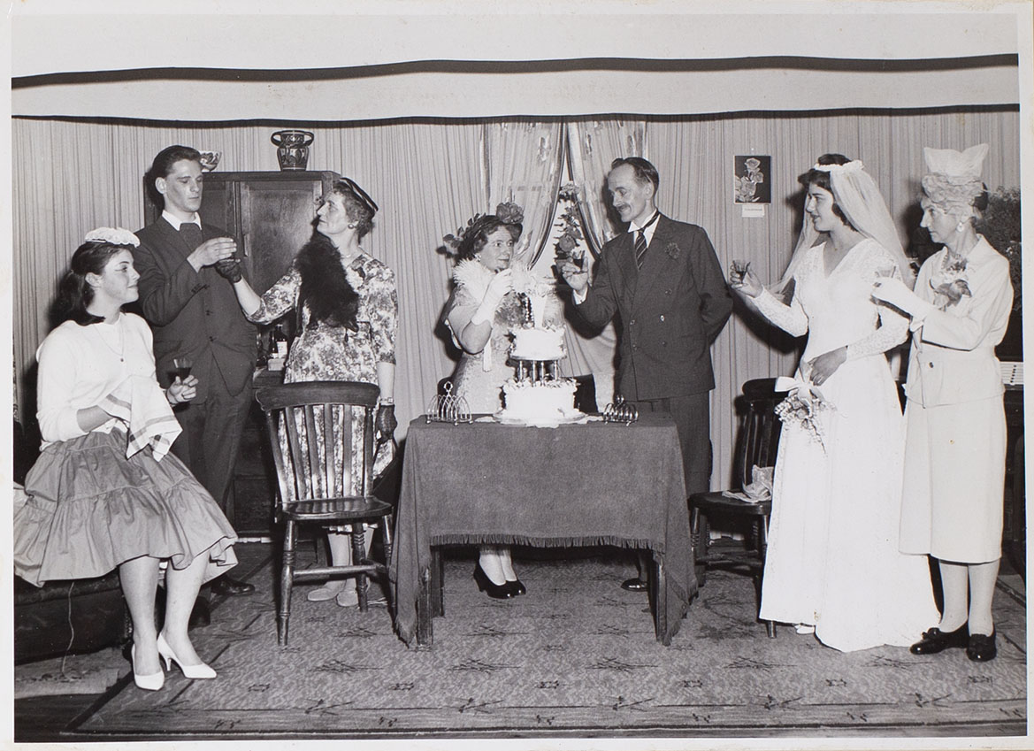 Photograph of Bishopsteignton Players, drinking a toast at the wedding reception in the play 'Orange Blossom'