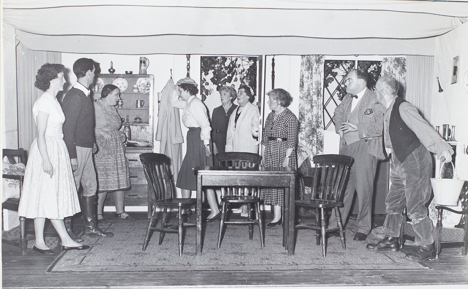 Photograph of the actors in a scene from the 1960s play 'The Camel's Back' performed by the Bishopsteignton Players