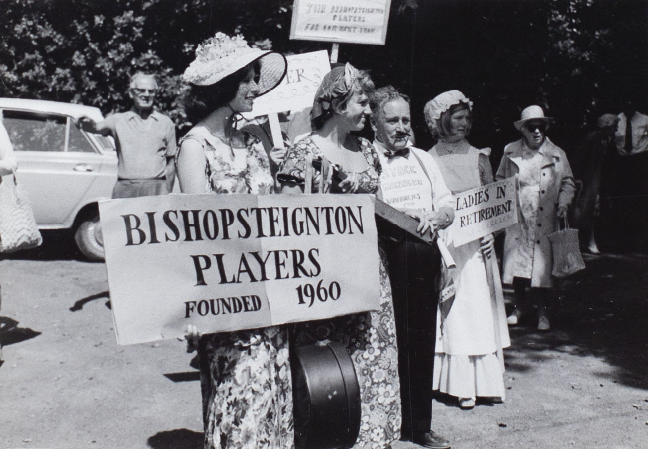 Photograph of some of the Bishopsteignton Players at the Church Fete 1974 showing a banner 'Bishopsteignton Players Founded 1960' and a poster 'Ladies in Retirement'.